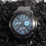 reloj con la caja negra y la correa de caucho negra con hebilla y la esfera negra y números árabes en azul